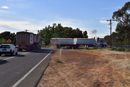 Curlwaa, NSW, Australia - November 10, 2017: Trucks with trailers usually named Road Trains on traffic light to enter single lane Abbotsford bridge over Murray river