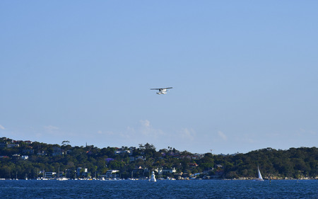 Sydney, NSW, Australia - October 29, 2017: Beach, homes and Bradleys Head lighthouse with seaplane