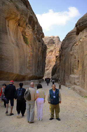 Petra, Jordan - March 06, 2019: Unidentified tourists and guide in canyon named As Siq to ancient Petra