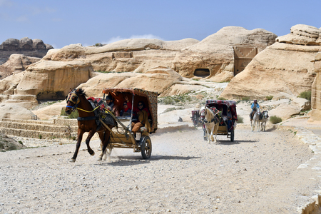 Petra, Jordan - March 06, 2019: unidentified tourists at Bab el-Siq and horse carriage in the Unesco World Heritage site of ancient Petra Editorial