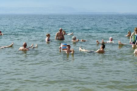 Mer Morte, Jordanie - 5 mars 2019 : Des personnes non identifiées aiment nager dans la mer Morte, un lac salé à 400 m sous le niveau de la mer, l'eau et la boue sont utilisées pour des traitements thérapeutiques et cosmétiques, les gens sont insubmersibles en raison du degré de salinité élevée