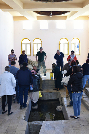 Wadi Musa, Jordan - March 06, 2019: Different tourists inside the building to take away water of Moses Spring Фото со стока - 122641859