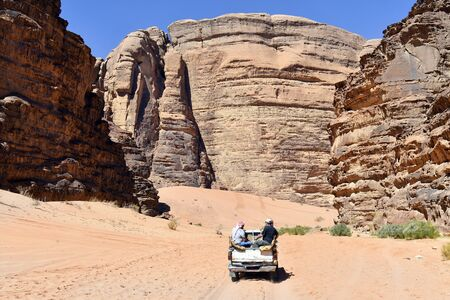 Jordan, Wadi Rum, unidentified tourists in pick-up car by sightseeing on unsealed road