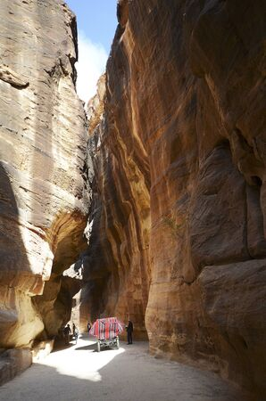 Petra, Jordan - March 06, 2019: Unidentified people and horse coach in narrow canyon named The Siq