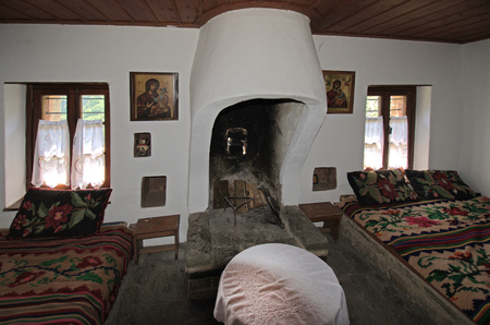 Greece, Epirus, living room with open fireplace in public medieval monastery Kipinas, built in 13th Century into rock face