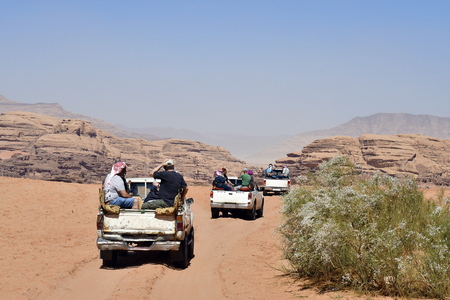 Jordan, tourists on pick-up cars, usual mode of transport in the UNESCO World heritage site of Wadi Rum in Middle East