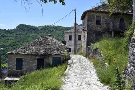 Greece, Epirus, paved path and homes with traditional stone roofs in mountain village of Tzoumerka, an Aromanian village in Pindos range, no transit possibility by cars