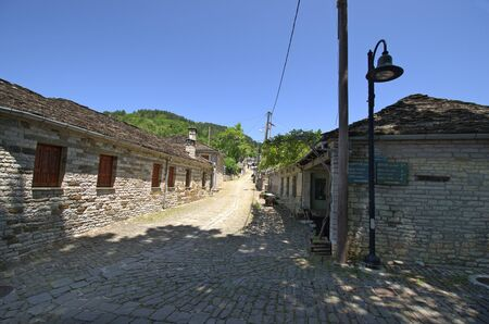 Greece, Epirus, paved road and homes built in traditional structure in mountain village Papigo in Vikos-Aoos national park