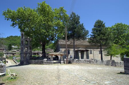 Greece, Epirus, paved square and church St. Vlasios built in 19th century in the mountain village of Papigo