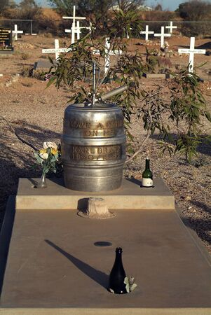 Coober Pedy, SA, Coober Pedy - April 13, 2010: Grave of  Karl Bratz with funny insription - have a drink on me - on beer barrel, situated on cemetery of the opal village in South Australia 新聞圖片