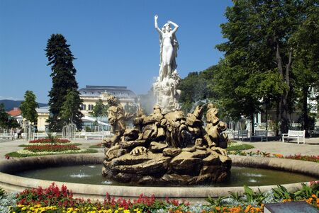 Baden, Austria - July 17, 2009: Undine Fountain in Kurpark with Casino in background