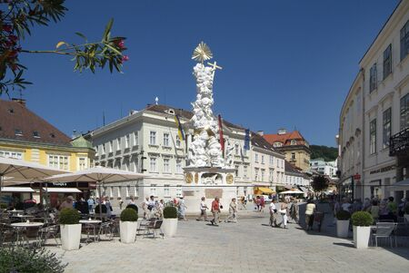 Baden, Austria - July 17, 2009: Unidentified people on townhall square with plaque column aka Holy Trinity column and town hall