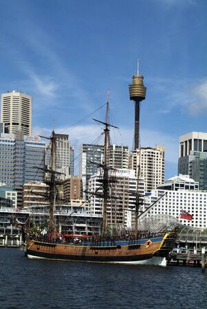 Sydney, Australia - February 11, 2008: HMS Endeavour - ship of discoverer Captain Cook, Maritime Museum in Darling Harbour and Sydney Tower aka Centrepoint Tower