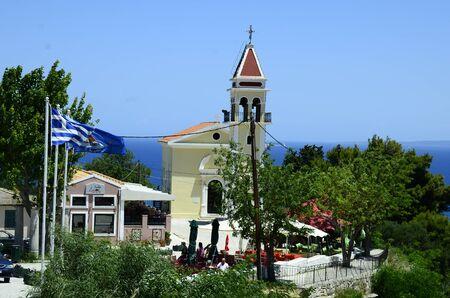 Zakynthos, Greece - May 26, 2016: Greece, Zakynthos Island, church Zoodochos Pigi and different flags over Zakynthos town 新聞圖片