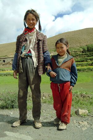 Tingri, China - July 11, 2004: Siblings in poor looking clothes at a rural village on Tingri Tableland in Tibet