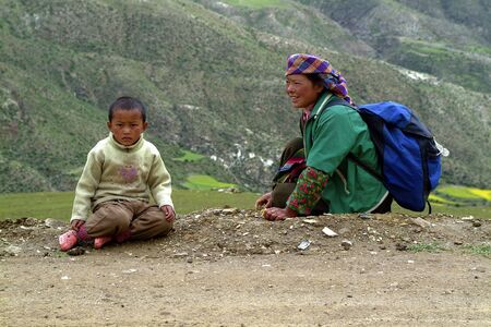 Shigatse, China - July 09, 2004: Unidentified Tibetians, mother with child rest on unsealed road 新聞圖片