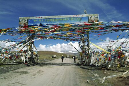 Gyatso La Pass, Tibet, China - July 11, 2004: Unidentified people rest on top of friendship highway from Lhasa to Nepal, decorated with prayer flags