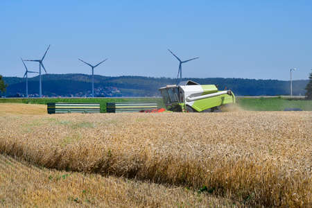 Austria, grain harvest of a wheat field with a combine harvester and wind turbines behind in Lower Austria