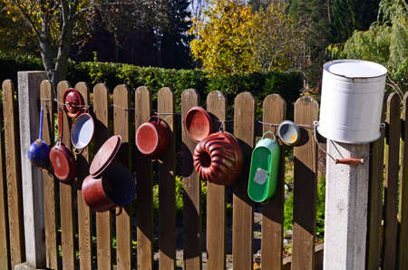 Austria, fence hung with kitchen utensils like pots and pans