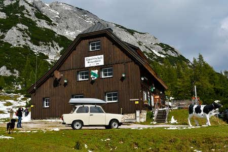 Tauplitz, Austria - September 24, 2017: Unidentified tourists, plastic cow and vintage car Trabant 601 the nickname was Trabi on Grazer mountain inn