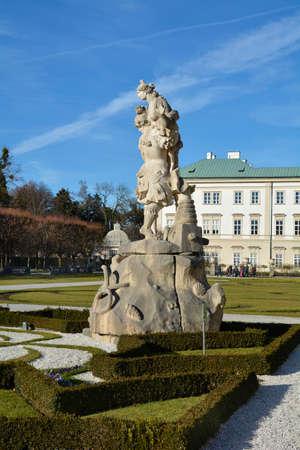 Salzburg, Austria - December 26, 2015: Unidentified people in Mirabell garden with sculpture and castle behind