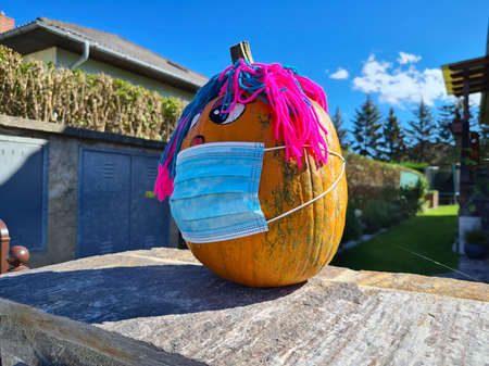 Reisenberg, Austria - October 04, 2020: Funny painted and decorated pumpkin with mask, a humorous reference to the covid 19 pandemic