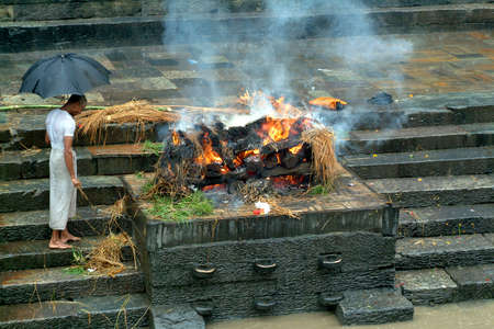 Pashupatinath, Nepal - July 15, 2004: Unidentified priest at traditional cremation, a common form of burial in hinduism 新聞圖片