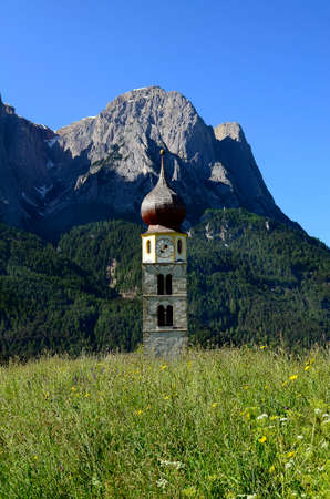 Seis, Italy, church spire of St. Valentin with Punta Santner mountain