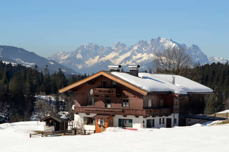 Austria, farmhouse built in traditional Tyrolean style in snowy landscape with mauntain named Wilder Kaiser in background 報道画像