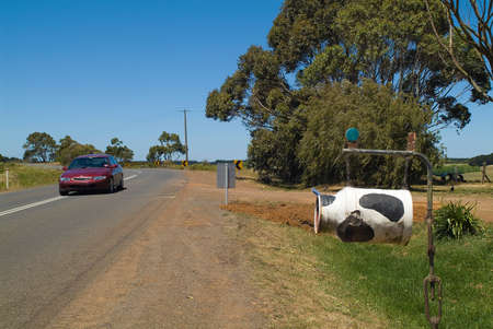 Australia, farm in Victoria with painted milk can as mailbox and car on road