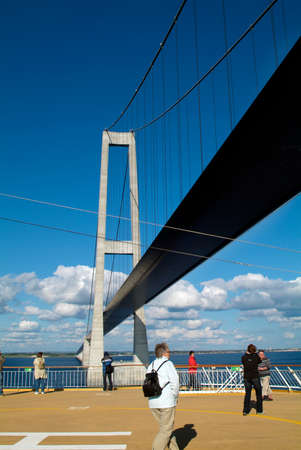 Denmark - June 05, 2009: Unidentified passengers on ferry passing under Storebæltsbroen the bridge over the Great Belt for vehicles and trains, a toll bridge between Zealand and Funen