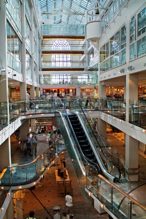 Oslo, Norway - June 21, 2009: Unidentified people in modern shopping center with escalator in Aker Brygge district