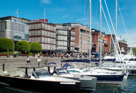 Oslo, Norway - June 21, 2009: Unidentified people enjoy a sunny day on promenade in Aker Brygge district Editorial