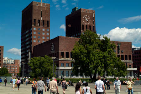 Oslo, Norway - June 21, 2009: Unidentified people and town hall with big clock on building wall