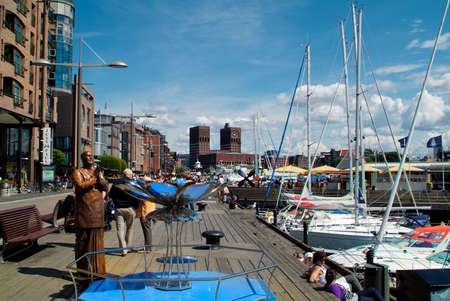 Oslo, Norway - June 21, 2009: Unidentified people enjoy a sunny day on promenade in Aker Brygge district with town hall in background