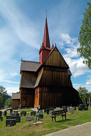 Ringebu, Norway - June 06, 2009: old stave church covered with wooden shingles and cemetery