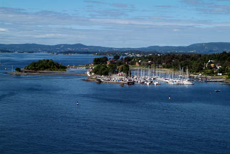 Norway, settlement with tiny yacht harbor on coastline along the Oslofjord Editorial