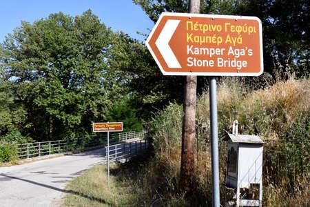 Greece, signs to the ancient stone bridge Kamber Aga aka Kamper Aga crossing Zagoritikos river, traditional memorial shrine on side