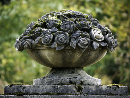 stone bowl: Stone bowl with roses on the forest cemetery Stock Photo