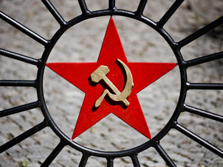 signifier: red star with hammer and sickle on fence door Stock Photo