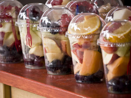 fruit salad in plastic cups on a wooden table
