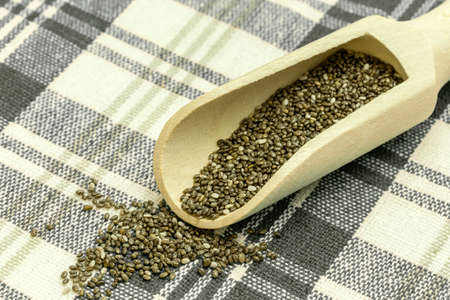 considerably: Chia seeds in a wooden spoon - Chia is a plant from Mexico and it is considered very healthy. The seeds contain a high percentage of omega-3 fatty acids, vitamins, antioxidants, proteins and minerals. Chia seeds swell considerably on and are suitable for  Stock Photo