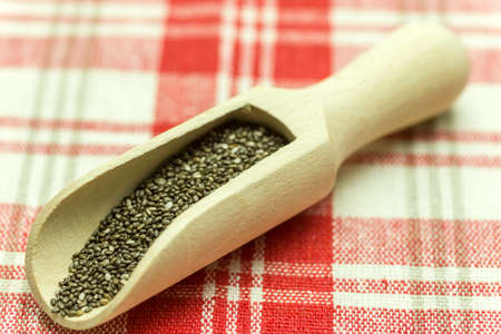 Chia seeds in a wooden spoon - Chia is a plant from Mexico and it is considered very healthy. The seeds contain a high percentage of omega-3 fatty acids, vitamins, antioxidants, proteins and minerals. Chia seeds swell considerably on and are suitable for  Stock Photo