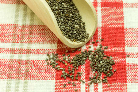plant antioxidants: Chia seeds in a wooden spoon - Chia is a plant from Mexico and it is considered very healthy. The seeds contain a high percentage of omega-3 fatty acids, vitamins, antioxidants, proteins and minerals. Chia seeds swell considerably on and are suitable for  Stock Photo
