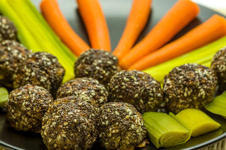 leeks: Meatballs with chia seeds and sesame on a plate with carrots and leeks