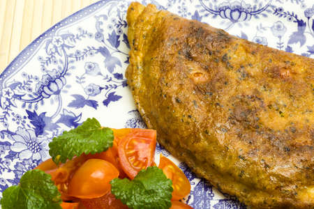 melissa: Omelet with chia seeds, melissa and tomato salad Stock Photo