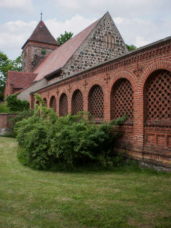 belongs: Radensleben is located along Route 164 (L164) between Wustrau and Herzberg north-west of Berlin. The place belongs since 1993 to Neuruppin - medieval village church with Campo Santo Stock Photo