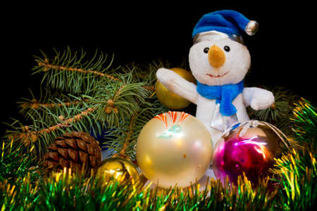 Dressed in a blue hat and scarf snowman surrounded by Christmas toys, shiny green tinsel and Christmas trees on a black background Stock Photo