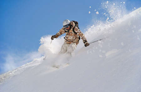 Skier in deep snow  In turn raises the snow dust