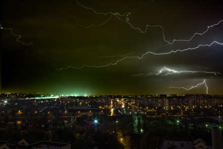 Lightning over the city at night with lights